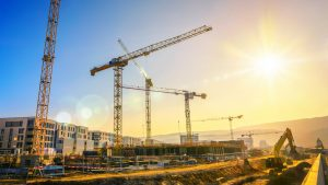 Large construction site including several cranes, with clear sky and the sun, construction consultant